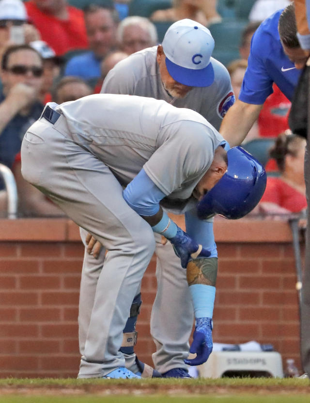 Chicago Cubs' Javier Baez, front, doubles over as he is checked on by manager Joe Maddon after being hit by a pitch during the third inning of a baseball game against the St. Louis Cardinals Sunday, June 17, 2018, in St. Louis. Baez left the game. (AP Photo/Jeff Roberson)