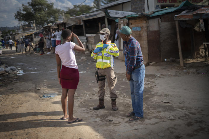 A South African police officer speaks to residents of the densely populated Alexandra township east of Johannesburg Friday, March 27, 2020. South Africa went into a nationwide lockdown for 21 days in an effort to mitigate the spread to the coronavirus, but in Alexandra, many people were gathering in the streets disregarding the lockdown. The new coronavirus causes mild or moderate symptoms for most people, but for some, especially older adults and people with existing health problems, it can cause more severe illness or death.(AP Photo/Jerome Delay)