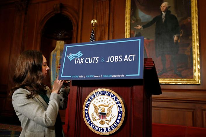 """A House staff member affixes a sign that says """"Tax Cuts and Jobs Act"""" ahead of a gathering of House Republicans making statements to the media following a vote on the GOP tax overhaul bill, Thursday, Nov. 16, 2017, on Capitol Hill in Washington. (AP Photo/Jacquelyn Martin)"""
