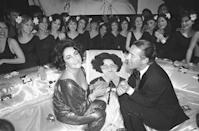 <p>Hollywood film star Elizabeth Taylor at Studio 54 with designer Halston for a party celebrating her 46th birthday and the opening night of her film, <em>A Little Night Music. </em></p>