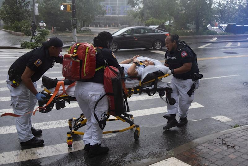 A person who was injured while trying to secure barriers meant to block flood waters at a building at Water and State Streets in lower Manhattan is transported after being injured (AP)