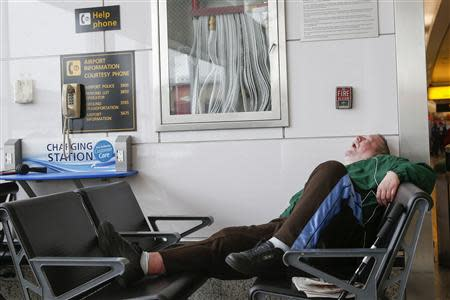 A man sleeps in a waiting area of the central terminal of LaGuardia Airport in the Queens borough of New York April 8, 2014. REUTERS/Shannon Stapleton