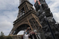 Visitors take a selfie at the main entrance during the opening up of the top floor of the Eiffel Tower, Wednesday, July 15, 2020 in Paris. The top floor of Paris' Eiffel Tower reopened today as the 19th century iron monument re-opened its first two floors on June 26 following its longest closure since World War II. (AP Photo/Francois Mori)