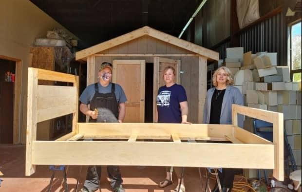 Tammy Denning, right, executive director of Blooming House, checks out one of the new beds with Blooming House operations manager Tavie Ingersoll and Habitat for Humanity construction manager Jamie MacKay. (Submitted by Tammy Denning - image credit)