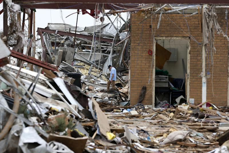 A man walks in the rubble of the Plaza Towers elementary school in Moore, Okla., Friday, May 24, 2013. (AP Photo/Sue Ogrocki)