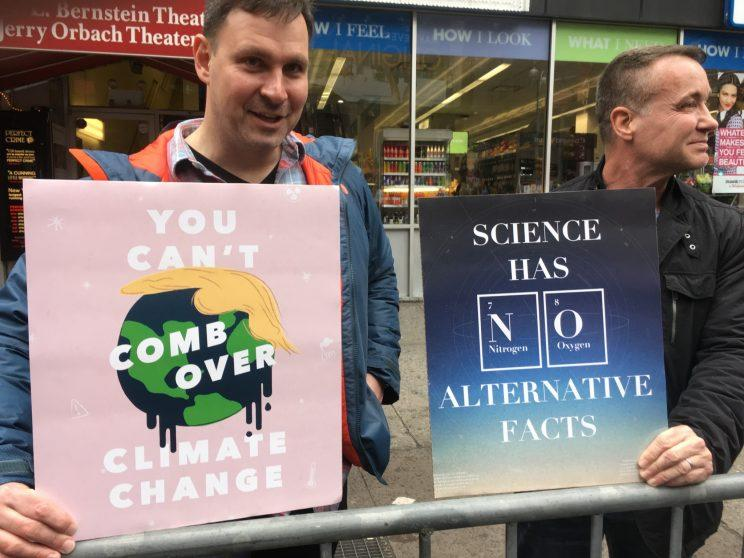 Two Science March demonstrators hold up their signs.