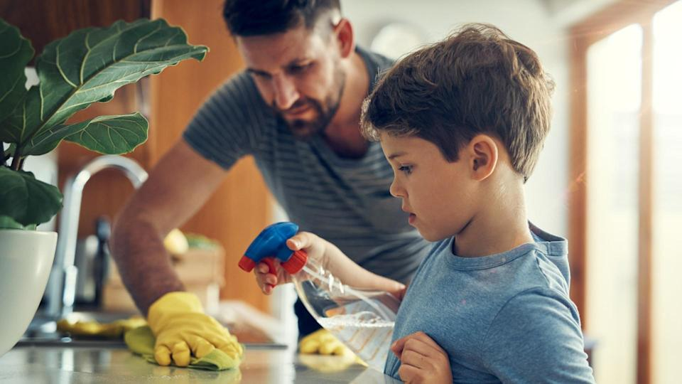 Shot of a father and son cleaning the kitchen counter together at home.