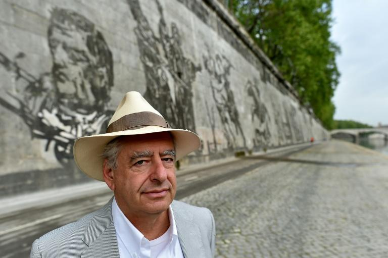 """South African artist William Kentridge poses in front of his mural """"Triumphs and Laments"""" -- a 550 meter-long fresco -- drawn in 2016 on the embankment walls that line the River Tiber in Rome"""