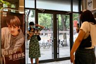 A superfan poses for photos next to a poster of Chinese singer Chen Junyu during a fan-organised birthday event (AFP/Jade GAO)
