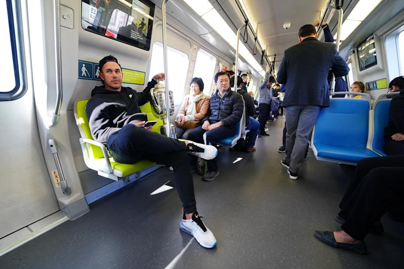 Brooks Koepka rides a BART train with the Wanamaker Trophy