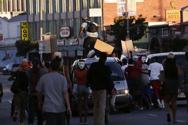 A protester stomps on a van during a demonstration in reaction to the acquittal of neighborhood watch volunteer George Zimmerman on Monday, July 15, 2013, in Los Angeles. Anger over the acquittal of a U.S. neighborhood watch volunteer who shot dead an unarmed black teenager continued Monday, with civil rights leaders saying mostly peaceful protests will continue this weekend with vigils in dozens of cities. (AP Photo/Jae C. Hong)