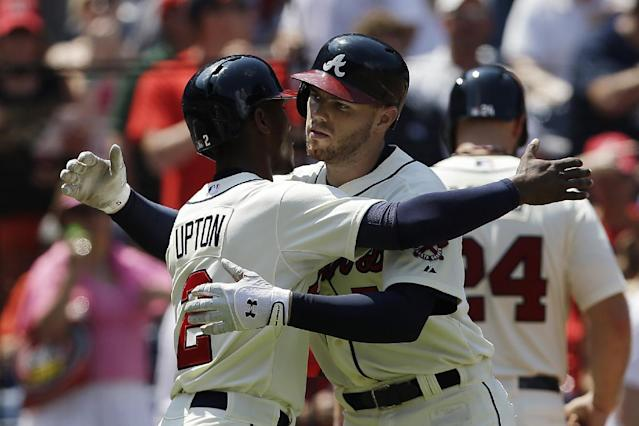 Atlanta Braves' Freddie Freeman, right, gets a hugs from teammate B.J. Upton after hitting three-run home run in the fifth inning of a baseball game against the Miami Marlins in Atlanta, Sunday, Aug. 11, 2013. (AP Photo/John Bazemore)