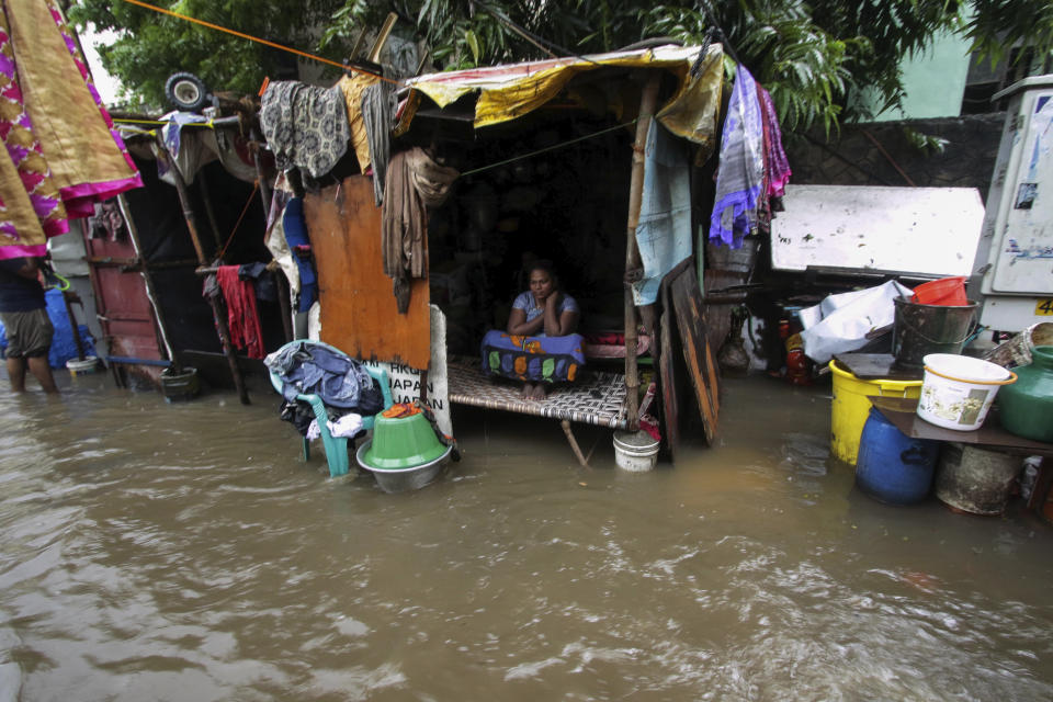 A woman sits inside her hut at a flooded street in Chennai, India, Wednesday, Nov.25, 2020. (AP Photo/R. Parthibhan)