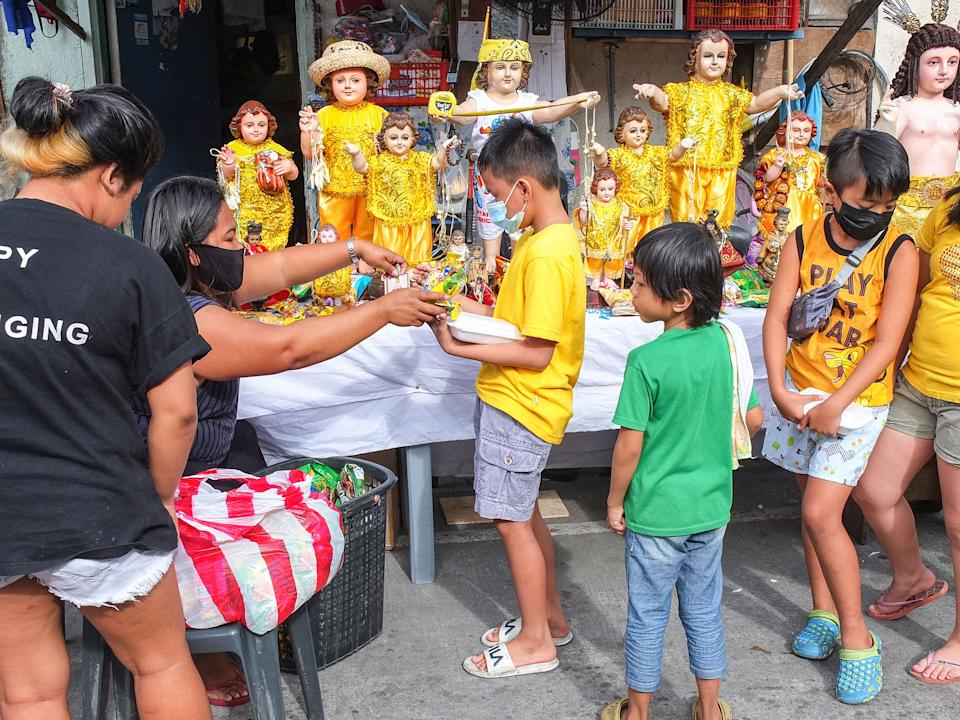 A good samaritan gives candies and food to Filipino children in Barangay Tañong, Malabon, Philippines. Filipino youth celebrates Feast of Santo Niño this year in a different kind of manner. Unlike in the past few years, with procession, parlor games and more. This year, it's a just simple activity like distribution of candies and goodies with only few participants because of the COVID-19 pandemic. (Photo by Josefiel Rivera/SOPA Images/LightRocket via Getty Images)