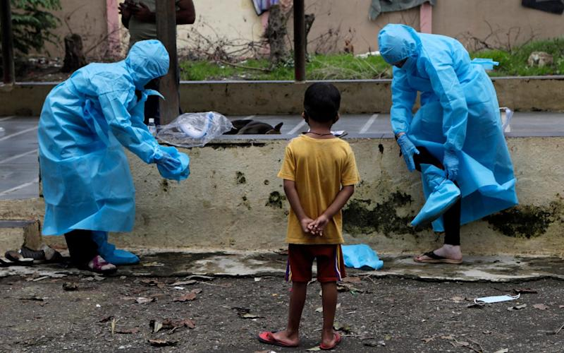 Health workers remove their protective gear after screening residents for symptoms at Devnar slum in Mumbai - AP
