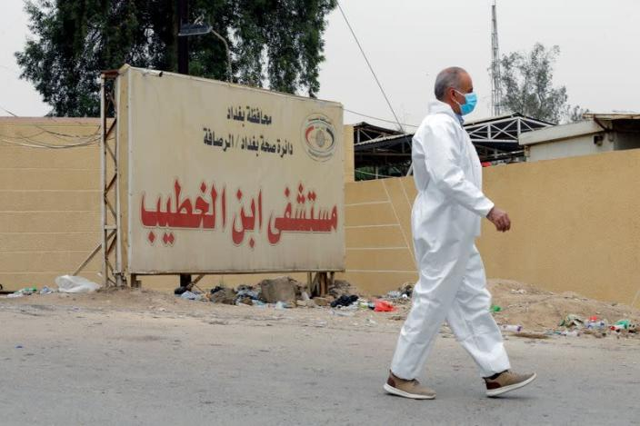 A medical staff member walks near the main entrance of Ibn Khatib hospital where a fire was sparked by an oxygen tank explosion, in Baghdad