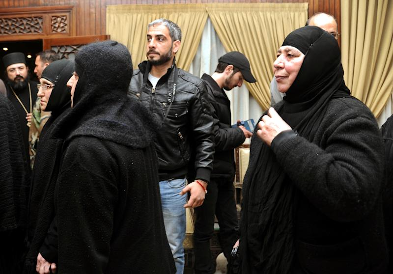 In this photo released by the Syrian official news agency SANA, a group of nuns, who were freed after being held by Syrian rebels, greet church officials at the Syrian border town of Jdeidat Yabous, early Monday, March. 10, 2014. Rebels in Syria freed more than a dozen Greek Orthodox nuns on Monday, ending their three-month captivity in exchange for Syrian authorities releasing dozens of female prisoners. The release of the nuns and their helpers, 16 women in all, is a rare successful prisoner-exchange deal between Syrian government authorities and the rebels seeking to overthrow the rule of President Bashar Assad. (AP Photo/SANA)