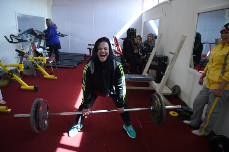 Parhiz strains during a deadlift exercise as teammate Sadya Ayubi looks on at a training session