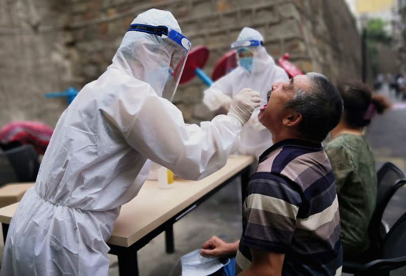 Medical worker collects swab from a man to conduct free nucleic acid tests for residents in the residential compound in Urumqi