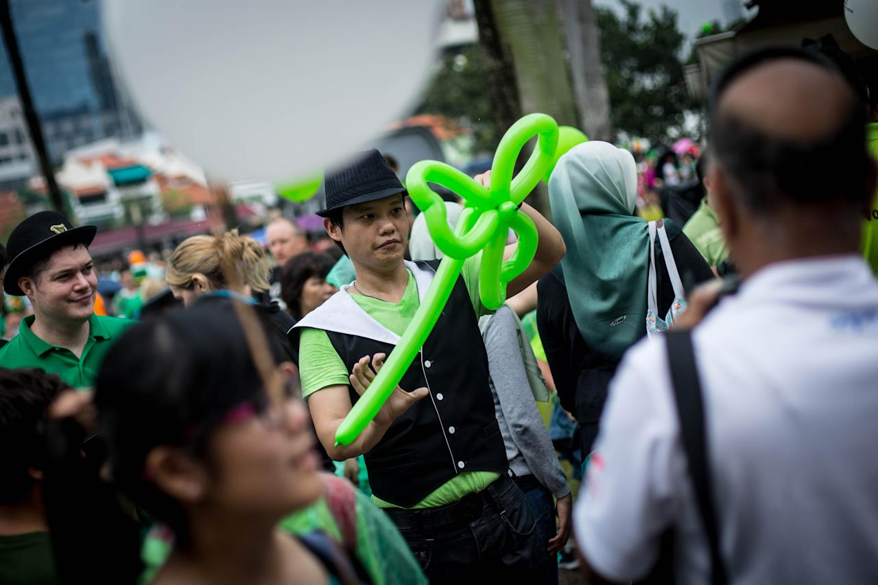 SINGAPORE - MARCH 17: A man makes Shamrock balloons prior to the start of the Singapore St Patricks Day Parade at Boat Quay on March 17, 2013 in Singapore. Singapore's Irish community gathered at Boat Quay for a three-day-long St Patrick's Day Street Festival which featured street performances, buskers, and Irish food and drink.  (Photo by Chris McGrath/Getty Images)