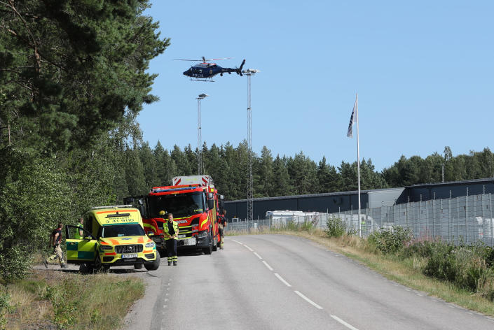 A large police operation with police, fire and rescue service and a police helicopter is underway outside Hallby Prison near Eskilstuna, Sweden, on Wednesday July 21, 2021. Two inmates are reported to have taken staff members hostage inside the prison. (Per Karlsson / TT via AP)