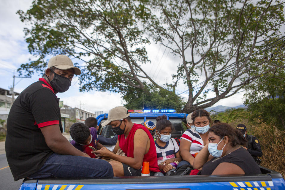 Honduran migrants sit in the bed of a police vehicle after they were detained in Chiquimula, Guatemala, Tuesday, Jan. 19, 2021. A once large caravan of Honduran migrants that pushed its way into Guatemala last week had dissipated by Tuesday in the face of Guatemalan security forces. (AP Photo/Oliver de Ros)