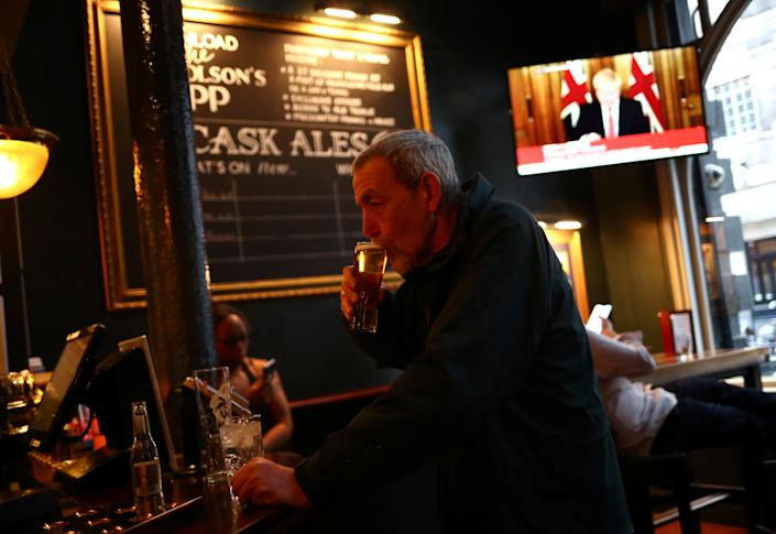 A man with a drink as Britain's Prime Minister Boris Johnson, is seen on a television screen in a pub in London as the spread of the coronavirus disease (COVID-19) continues. In Westminster, London, Britain March 20, 2020. REUTERS/Hannah McKay