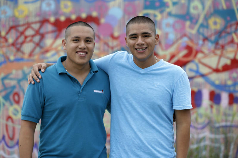 In this Wednesday, June 12, 2013 photo, brothers Jorge Tume, left, and Francis Tume are shown in Miami. Tume's parents brought them to the U.S. from Peru on tourist visas when they were young and decided to stay, becoming unauthorized immigrants with no legal status. Now, one year after President Barack Obama announced an executive order allowing young people living in the U.S. illegally to stay and work, nearly 300,000 young adults previously living illegally in the United States have been granted permission to stay and work through the program, the most significant shift in immigration policy in recent decades. (AP Photo/Wilfredo Lee)