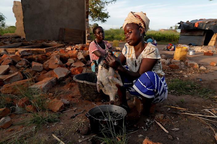 "Maria Jofresse, 25, watches her mother Ester Thoma preparing food beside their damaged house in the aftermath of Cyclone Idai, in the village of Cheia, which means ""Flood"" in Portuguese, near Beira, Mozambique April 4, 2019. (Photo: Zohra Bensemra/Reuters)"