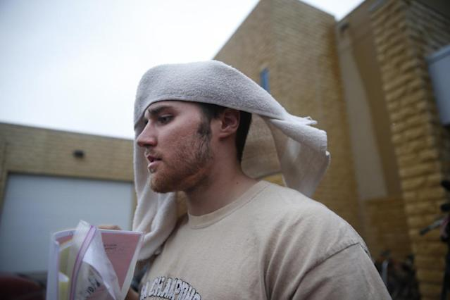 Former Minnesota quarterback Philip Nelson leaves the Blue Earth Co jail with a towel on his head after posting $20,000 bail in his assault case stemming from a fight outside a bar that left another former football player in critical condition with head injuries, in Mankato, Minn, Monday, May 12, 2014. Authorities say Nelson kicked Isaac Dallas Kolstad, 24, in the head after another man punched and knocked him to the ground early Sunday as bars were closing in Mankato. (AP Photo/The Star Tribune, Richard Tsong-Taatarii)