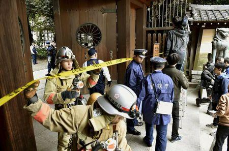 Police officers and fire fighters investigate at the south gate of Japan's controversial Yasukuni Shrine where there was an explosion and burned the ceiling and wall of the public bathroom, in Tokyo
