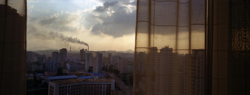 In this Aug. 7, 2012 photo, the sun sets over Pyongyang, North Korea, behind the curtained window of a downtown hotel room. (AP Photo/David Guttenfelder)