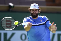 Reilly Opelka, of the United States, returns a shot to Taro Daniel, of Japan, at the BNP Paribas Open tennis tournament Saturday, Oct. 9, 2021, in Indian Wells, Calif. (AP Photo/Mark J. Terrill)