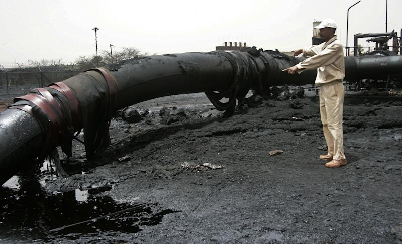 In this Tuesday, April 24, 2012 photo, a Sudanese worker inspects burnt out oil pipes at the oil-rich border town of Heglig, Sudan. The African Union says Sudan must stop the aerial bombardment of South Sudan and has called on both countries to cease hostilities immediately. (AP Photo/Abd Raouf)