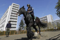 Mikhi Fearon, 17, rides Molly watched by instructor Tom Warmerdam, during a riding lesson at Ebony Horse Club in Brixton, south London, Sunday, April 18, 2021. In the midst of south London's hustle and bustle, only a 10-minute walk from a subway station, is a school where children are encouraged to horse around. The Ebony Horse Club provides 140 rides per week to children in the local community offering them the opportunity to learn important life skills along with horseback riding. (AP Photo/Kirsty Wigglesworth)