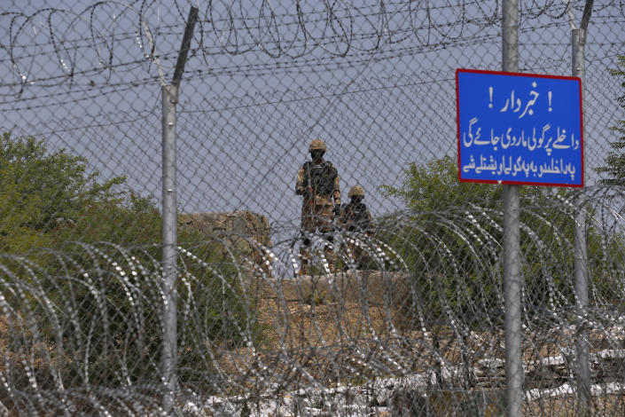 Pakistan Army troops patrol along the fence with a warning board read as 'Beware, Entrance will be shot' on the Pakistan Afghanistan border, in Khyber district, Pakistan, Tuesday, Aug. 3, 2021. Pakistan's military said it completed 90 percent of the fencing along the border with Afghanistan, vowing the remaining one of the most difficult tasks of improving the border management will be completed this summer to prevent any cross-border militant attack from both sides. (AP Photo/Anjum Naveed)
