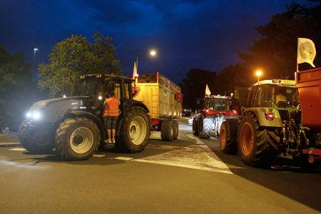 French farmers and their tractors with FNSEA farmer's union flags block a road in Feyzin