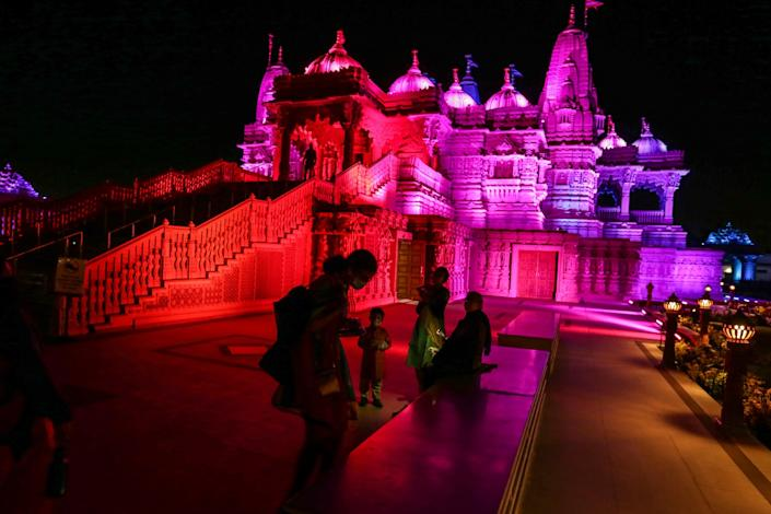 A family outside a Hindu temple bathed in red, purple and blue light
