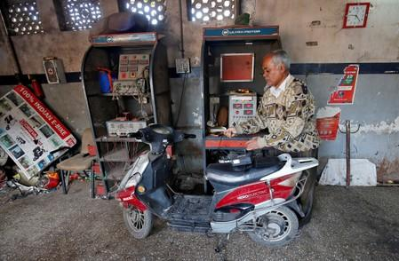 FILE PHOTO: A worker checks the power supply to recharge an electric scooter inside a workshop in Ahmedabad