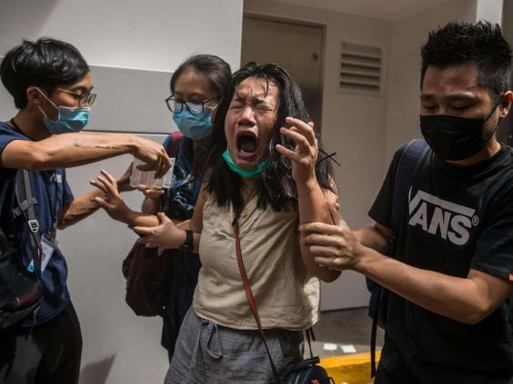 A woman reacts after she was hit with pepper spray deployed by police as they cleared a street with protesters rallying against a new national security law in Hong Kong on July 1, 2020. (Dale De La Rey/AFP via Getty Images)