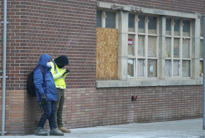 A pair of workers wear masks while waiting for a ride outside a construction site late Monday, Dec. 28, 2020, in downtown Denver. (AP Photo/David Zalubowski)