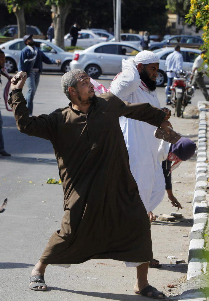 An Egyptian protester throws stones at the residence of Iran's top diplomat in Cairo, Egypt, Friday, April 5, 2013. Dozens of mostly ultraconservative protesters threw rocks Friday at the residence of Iran's top diplomat in Cairo to protest the Egyptian government's attempt to improve ties with Tehran.(AP Photo/Amr Nabil)