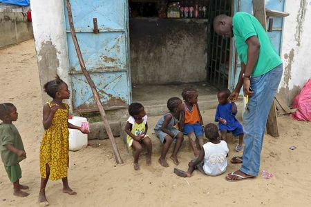 Mamadou Ka greets children near his family home after being repatriated last month from Gabon, in Dakar