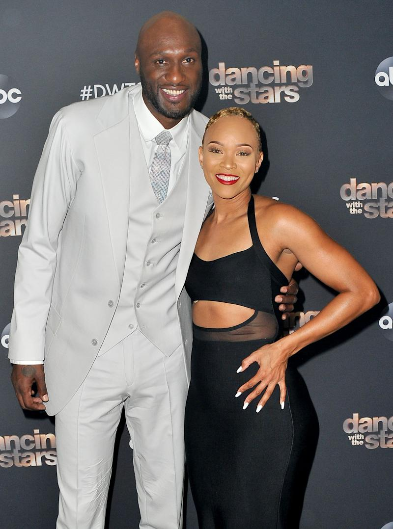 Lamar Odom and Sabrina Parr pose at an event