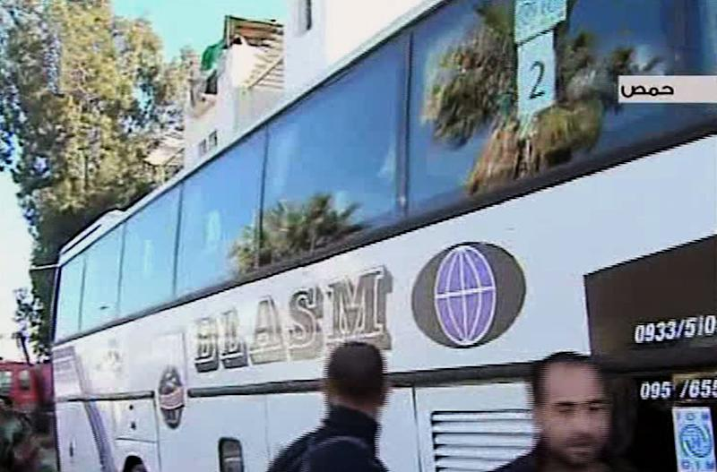 In this video image released by the Syrian official news agency SANA, Syrian citizens sit aboard a bus after they evacuated the besieged rebel-held neighborhood of of Jouret el-Shayah, in Homs province, Syria, Friday, Feb. 7, 2014. The Syrian government on Friday began evacuating civilians trapped in rebel-held parts of a battleground city under a rare deal struck between the government and the opposition that also included a three-day cease-fire allowing humanitarian aid convoys to the besieged areas. (AP Photo/SANA)