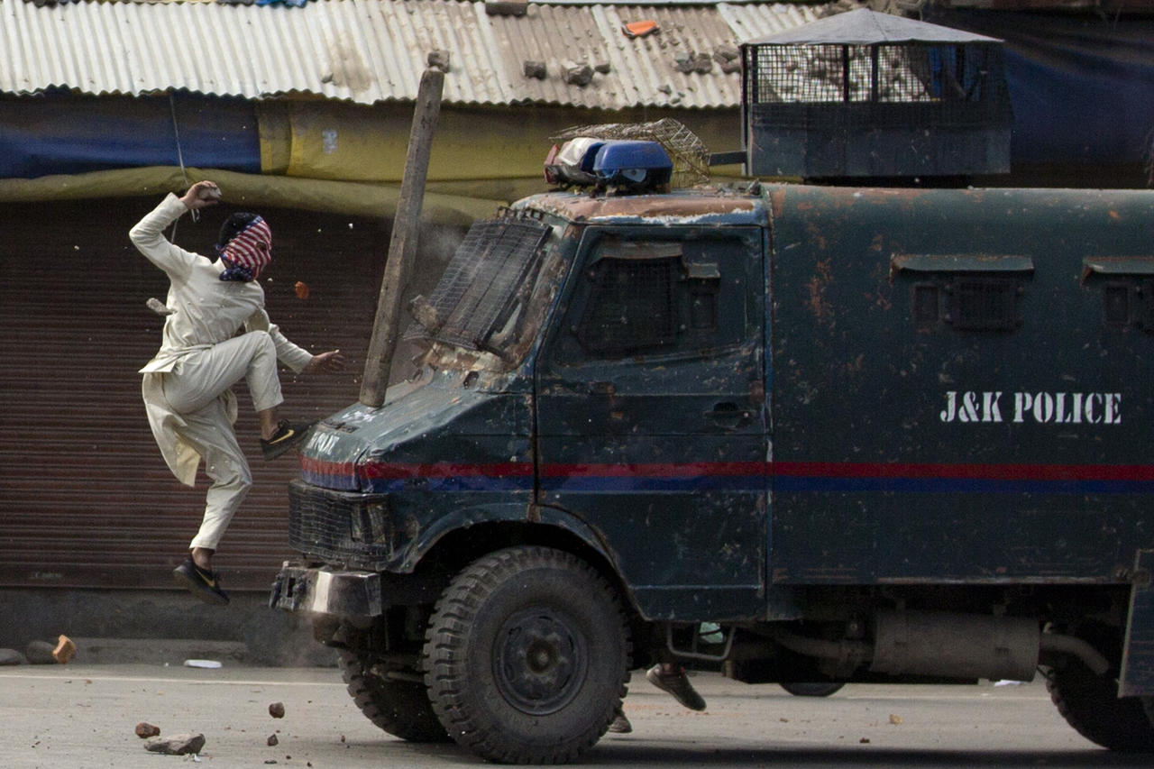 A masked Kashmiri protester jumps on an Indian police armored vehicle as he throws stones at it during a protest in Srinagar on May 31, 2019. (AP Photo/Dar Yasin)