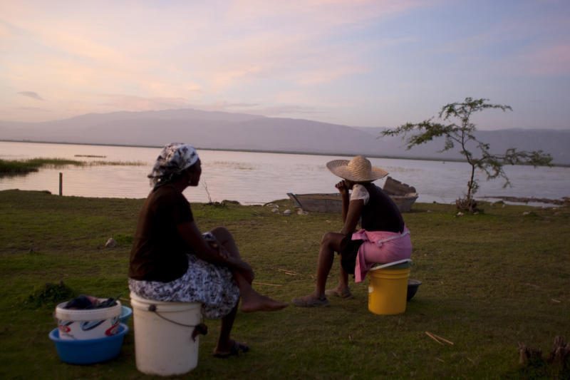 In this Aug. 22, 2013 photo, vendors Jacline Bienheme, left, and Marie Jolerme wait for fishermen to return on the shores of Lake Azuei in Thomazeau, Haiti. Experts are sounding a new alarm about the effects of climate change for parts of the Caribbean: the depletion of already strained drinking water throughout much of the region. (AP Photo/Dieu Nalio Chery)