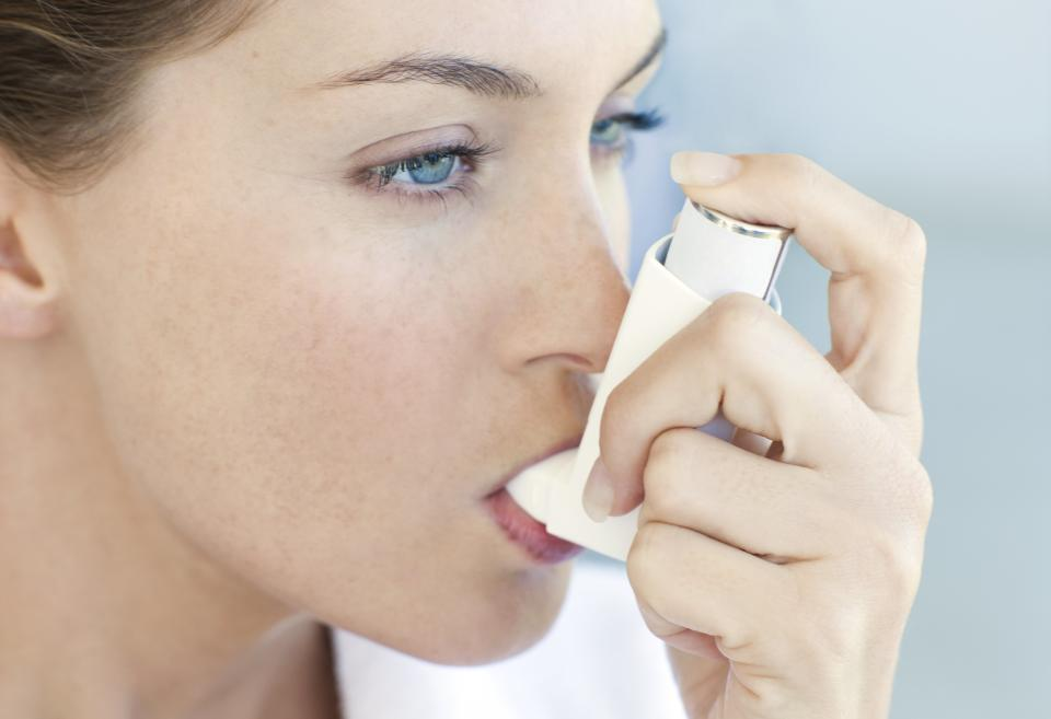 Woman with asthma using an inhaler for relief.