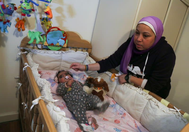 Yasmina al-Habbal, sits next to her Ghlaya, an orphan she sponsors, at her home in Cairo