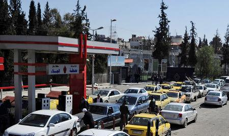 Vehicles queue for petrol at a gas station in Damascus